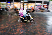 In Utrecht rijdt een stelletje op een scooter door de regen.<br /> <br /> In Utrecht a couple is riding on a scooter in the rain.