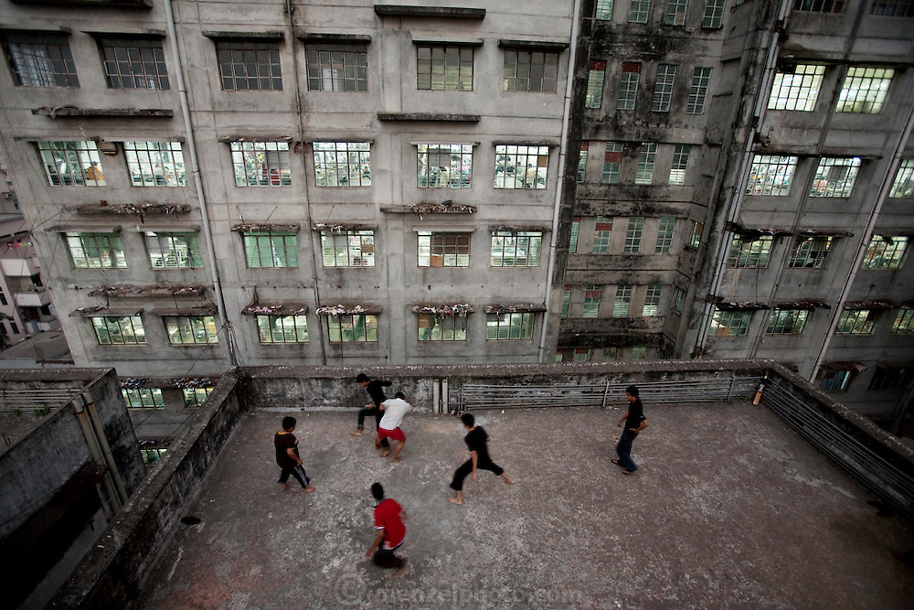 Young men play cricket and soccer on the roof of a building next to the Ananta Clothing Factory on Elephant Road in Dhaka, Bangladesh. (From the book What I Eat Around the World in 80 Diets.)
