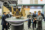 A group of naval cadets are shown a turret mounted gun system on the Konsberg stand - The DSEI (Defence and Security Equipment International) exhibition at the Excel Centre, Docklands, London UK 15 Sept 2015
