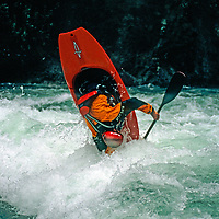 A master kayaker performs tricks in waves on the Kananskis River.