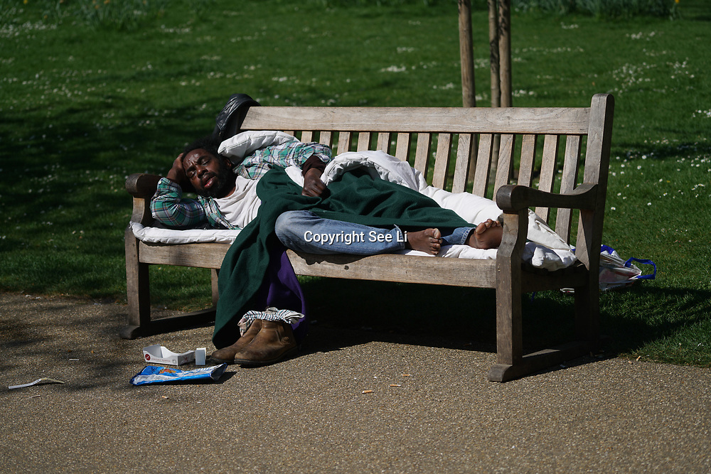 London,England,UK.9th April 2017. A homeless man sleeping on the bench  in St James Park, London,UK. by See Li