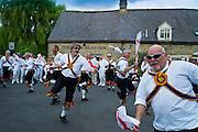 Morris dancers, Brighton Morris Men, perform a dancing display at The Kings Head Pub in Bledington, Oxfordshire, UK