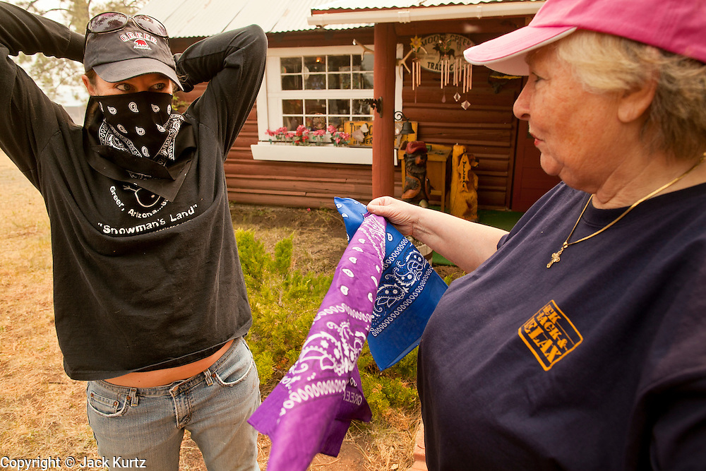 """05 JUNE 2011 - GREER, AZ:  Kristi Spillman (CQ LEFT) and Judy Cline (CQ) talk and put on bandanas before leaving their businesses in Greer Sunday. Spillman operates the Frosty Bottom Cafe and Cline the """"Quacker Barrel"""" (CQ QUACKER) The fire grew to more than 180,000 acres by Sunday with zero containment. A """"Type I"""" incident command team has taken command of the fire.  PHOTO BY JACK KURTZ"""