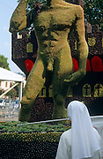 A nun looks up at a giant  grape-covered figure resembling Michelangelo's David sculpture, at a grape harvest festival in the Euganeian Hills area of Veneto, Italy