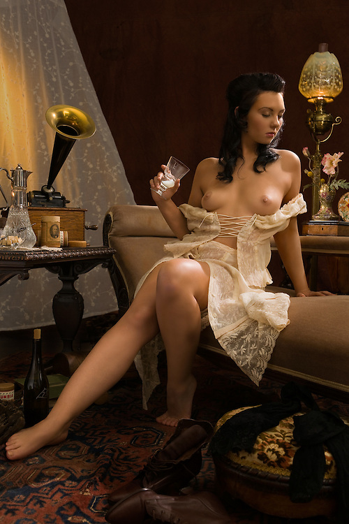 Scene set in Paris circa Paris 1910. A beautiful young woman listens to music while enjoying a glass of absinthe abandoning herself to her sensuality. Model - Sabrina Sin