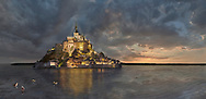 """Scenic view of the tidal island  of Mont Saint Michel at night at high tide surrounded and its medieval abbey of Saint Michel. Normandy France.<br /> <br /> The tides vary greatly, at roughly 14 metres (46 ft) between highest and lowest water marks. Popularly nicknamed """"St. Michael in peril of the sea"""" by medieval pilgrims making their way across the flats, the mount can still pose dangers for visitors who avoid the causeway and attempt the hazardous walk across the sands from the neighbouring coast. .<br /> <br /> Visit our MEDIEVAL PHOTO COLLECTIONS for more   photos  to download or buy as prints https://funkystock.photoshelter.com/gallery-collection/Medieval-Middle-Ages-Historic-Places-Arcaeological-Sites-Pictures-Images-of/C0000B5ZA54_WD0s"""
