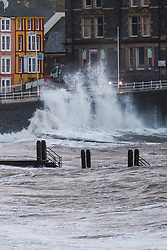 © Licensed to London News Pictures. 16/01/2018. Aberystwyth, UK. Gale force winds and the high tide combine to bring stormy seas and huge waves crashing in to the sea defences and lighthouse  in Aberystwyth, on the Cardigan Bay coast of west wales at first light today. The Met Office has issued a yellow warning for wind covering  all of the UK on Wednesday and into Thursday, with gusts expected to reach 60-70mph in may exposed places, causing widespread disruption to travel and a risk of damage to properties .Photo credit: Keith Morris/LNP