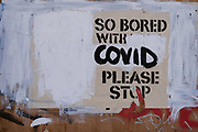 An altered message on the outside of a closed business on Charing Cross Road, stating the writer's boredom with Covid restrictions, during the third lockdown of the Coronavirus pandemic, on 30th March 2021, in