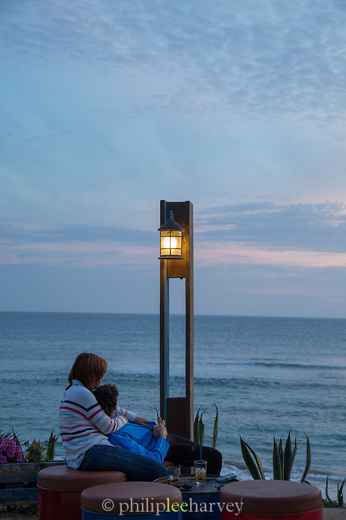 Young couple sitting together and looking at sea at dusk, Cadiz, Andalusia, Spain