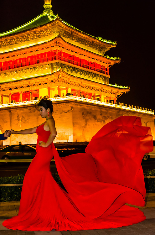 A bride poses for a wedding photo in front of The Bell Tower, built in 1384 during the early Ming Dynasty, is a symbol of the city of Xi'an and one of the grandest of its kind in China. The Bell Tower also contains several large bronze-cast bells from the Tang Dynasty. Xi'an, Shaanxi Province, China.