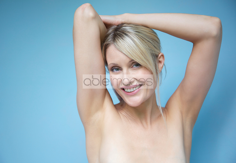 Smiling Woman with Arms Crossed above Head