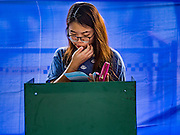 07 AUGUST 2016 - BANGKOK, THAILAND:  A Thai woman looks at her ballot in a polling place at Wat That Thong in Bangkok. Thais voted Sunday in the referendum to approve a new charter (constitution) for Thailand. The new charter was written by a government appointed panel after the military coup that deposed the elected civilian government in May, 2014. The charter referendum is the first country wide election since the coup.      PHOTO BY JACK KURTZ