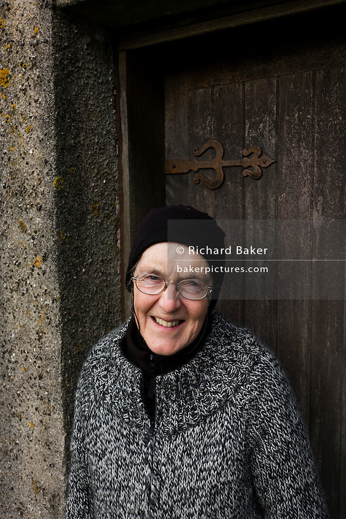 Portrait of caretaker Marina Carrier, at the doorway of the old church at Kilninian (built 1755, ten years after the Jacobite Rising)  but the site of worship with medieval tombstones dating from the 14th century, Kilninian, Isle of Mull, Scotland. church is one of the oldest, and until very recently, still used for worship.   Possibly standing on the site of an earlier medieval church, it first appears in the records of 1561, where it is stated that the parsonage of 'Keilnoening' had formerly belonged to the Abbot of Iona, one-third of the revenues going to the Bishop of the Isles as was customary in the diocese. Iona Abbey would have appointed a minister for the church at a stipend lower than the tithes. It is uncertain whether the church was dedicated to St Ninian, the apostle of Galloway, or to a local saint of the Early Christian period'.   It is also believed to have been once known as the Chapel of the Nine Maidens and in Gaelic  'Cill Naoi Nighean', although another possible name was The Church of the Holy Maidens - 'Cill Naoimh Nighean...(http://www.undiscoveredscotland.co.uk/mull/kilninianchurch/index.html)