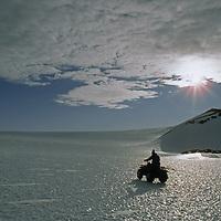 Patriot Hills, Ellsworth Mountains, Antarctica.An explorer drives an ATV across a shimmering bare ice glacier.