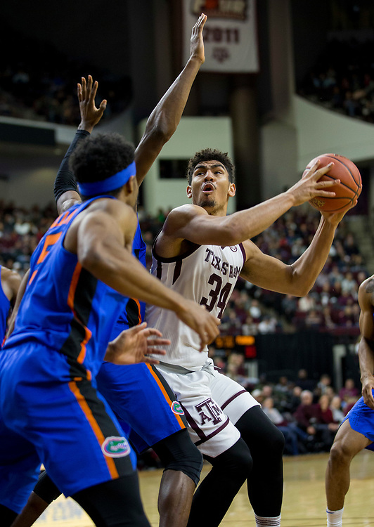 Texas A&M center Tyler Davis (34) looks to shoot against Florida defenders during the first half of an NCAA college basketball game Tuesday, Jan. 2, 2018, in College Station, Texas. (AP Photo/Sam Craft)