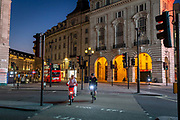 Two people on bicycles ride acorss an almost deserted Picadilly Circus in London on March 27th, 2020. The centre of London is extremely quiet with almost every business closed and very few people about because of the Governments lockdown measures due to the Coronavirus crisis.