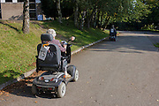 A couple riding on rented mobility scooters in the grounds of the Yorkshire Sculpture Park.