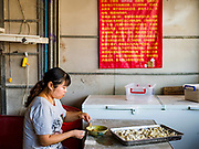 """14 FEBRUARY 2019 - SIHANOUKVILLE, CAMBODIA:  A Chinese woman makes small noodle dumplings in a Chinese noodle shop in Sihanoukville. There are thousands of Chinese workers in Sihanoukville who work to support the casino and hotel industry in the town. There are about 80 Chinese casinos and resort hotels open in Sihanoukville and dozens more under construction. The casinos are changing the city, once a sleepy port on Southeast Asia's """"backpacker trail"""" into a booming city. The change is coming with a cost though. Many Cambodian residents of Sihanoukville  have lost their homes to make way for the casinos and the jobs are going to Chinese workers, brought in to build casinos and work in the casinos.      PHOTO BY JACK KURTZ"""