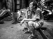 """29 DECEMBER 2018 - BANGKOK, THAILAND: A man takes a smoke break while making longevity noodles in his family shophouse. The family has been making traditional """"mee sua"""" noodles, also called """"longevity noodles"""" for three generations in their home in central Bangkok. They use a recipe brought to Thailand from China. Longevity noodles are served on special occasions, especially Chinese New Year, which is February 4, 2019.        PHOTO BY JACK KURTZ"""