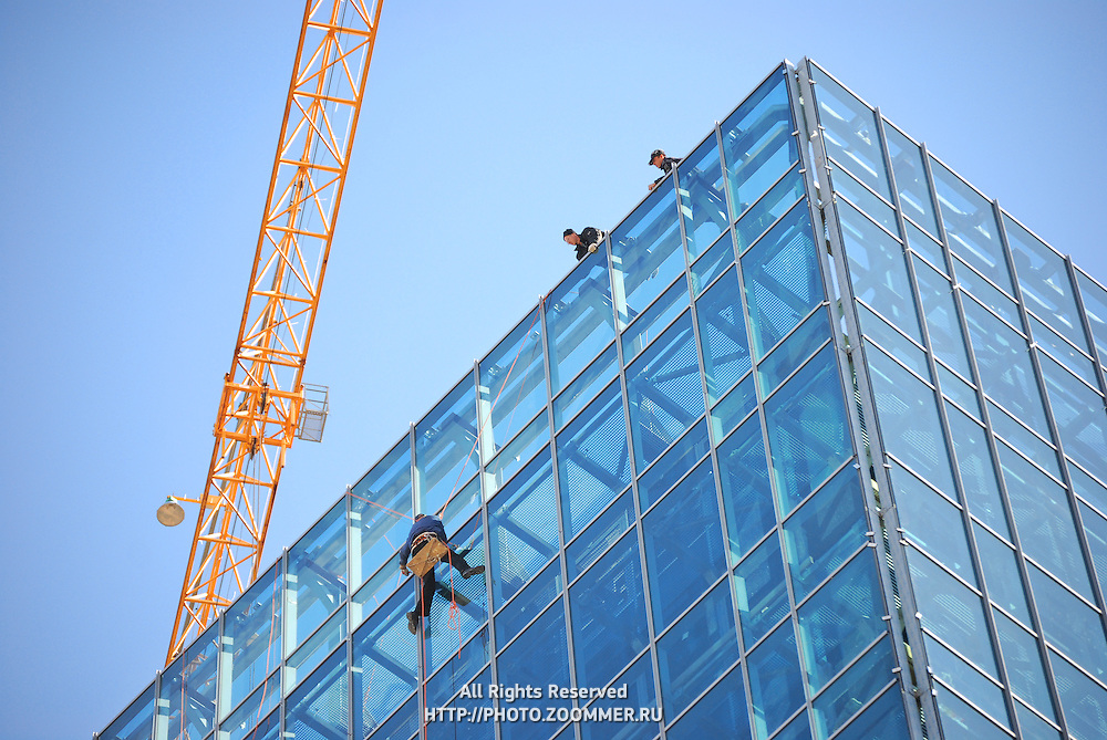 Building construction with crane and people on roof working and washing glass windows