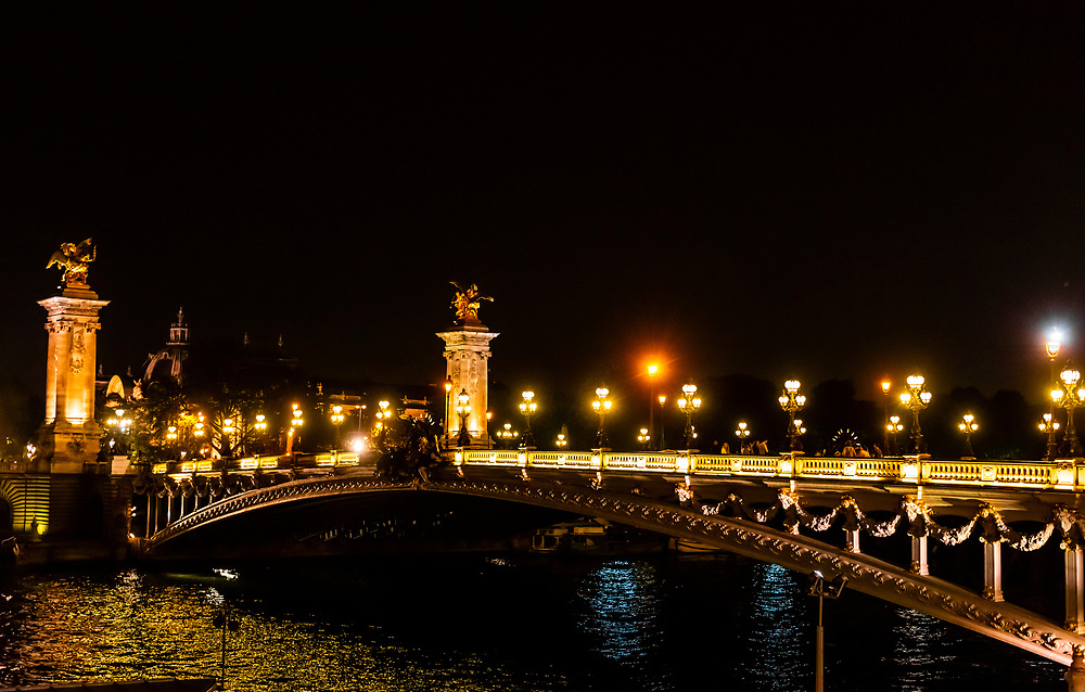 Pont Alexandre III (bridge) across the Seine River, at night. The bridge is the most ornate in the city and features art nouveau lamps, cherubs, nymphs and on the two large gilded sculptures at the end, winged horses. Paris, France.