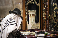 A man in a tallit, prays in front of the Aron Kodesh at the Western Wall. The Torah ark it is generally a receptacle, or ornamental closet, which contains each synagogue's Torah scrolls. This Aron has the capacity for over one hundred Torah scrolls and is decorated with drapes representing the second temple, who was destroyed in AD 70 when Jews were sent to exile.