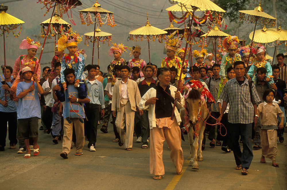 Procession with young boys dressed up as princes during Poy Sang Long, the yearly ordination of novice monks, Mae Hong Son, Thailand. April 2003. The invisible guardian spirit of the town rides on the horse in front.