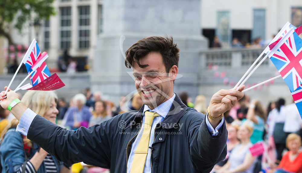 Trafalgar Square, London, June 12th 2016. Rain greets Londoners and visitors to the capital's Trafalgar Square as the Mayor hosts a Patron's Lunch in celebration of The Queen's 90th birthday. PICTURED: Satirical TV personality Jolyon Rubinstein encourages the crowd to wave their flags as he is filmed by a camera crew.