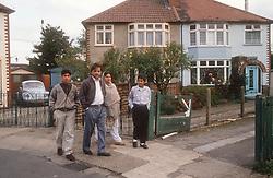 Family group walking along pavement outside semidetached houses,