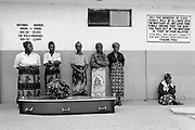 Members of the family of the deceased, Joyce Tembo, wait in line at the mortuary in Lusaka, Zambia to pick up her body after it had been prepared for burial by family members. She passed away on Saturday and is being buried on Tuesday, one of the busiest days of the week for funerals in Lusaka. A sign on the wall warns of misidentification, a problem when so many bodies are being prepared and picked-up on one day.