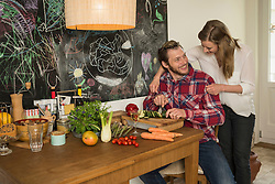 Man slicing vegetables on chopping board and his wife hugging from behind, Munich, Bavaria, Germany