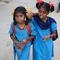 """Vijita (right) and Vijyashree Viswanathan head home to their fishing village after a day at the Government Girls High School, Venugopalapuram, Cuddalore...Vijita (age 14) and Vijyashree (age 11) Viswanathan lost their mother and brother to the tsunami in 2004. They continue to live in the fishing village of Thazanguda with their father Viswanathan, his second wife Kayalvizhi and their two children Sanjay (age 3) and Monica (age 1). ..Until the beginning of the 2009 academic year in June, Vijita and Vijyashree attended the local Thazanguda school. This village school teaches pupils only until the 8th Standard and with Vijita now entering the 9th, it was decided that the two daughters remain together and both travel 3km to the local town school: the Government Girls High School, Venugopalapuram in Cuddalore. ..At the same time Viswanathan decided he would cease day-to-day care of his daughters and place them in the Government Home for Tsunami Children, also in Cuddalore. This was not a move welcomed by either Vijita or Vijyashree and one afternoon after just two weeks at the orphanage, the two girls ran away. At roll call in the orphanage that evening the alarm was sounded and the two sisters were eventually located in Thazanguda waiting for their father and Kayalvizhi who were both away at the time. Realising his daughters' unhappiness, Viswanathan then took them out of the Government home. ..According to her class teacher, Vijita often compares her step-mother to her mother and concludes that she wants her mother back. Vijita confides in her teachers that her stepmother is forever demanding that she and her sister Vijyashree undertake housework. This frustration at home is tempered by the genuine love both sisters have for their father and two younger siblings Sanjay and Monica. Vijita expresses a lonelyness without her mother. Vijita's class teacher Pushpavalli concludes that """"Vijita wants something else beyond the love of her father and sister"""". ..Viswanathan appe"""