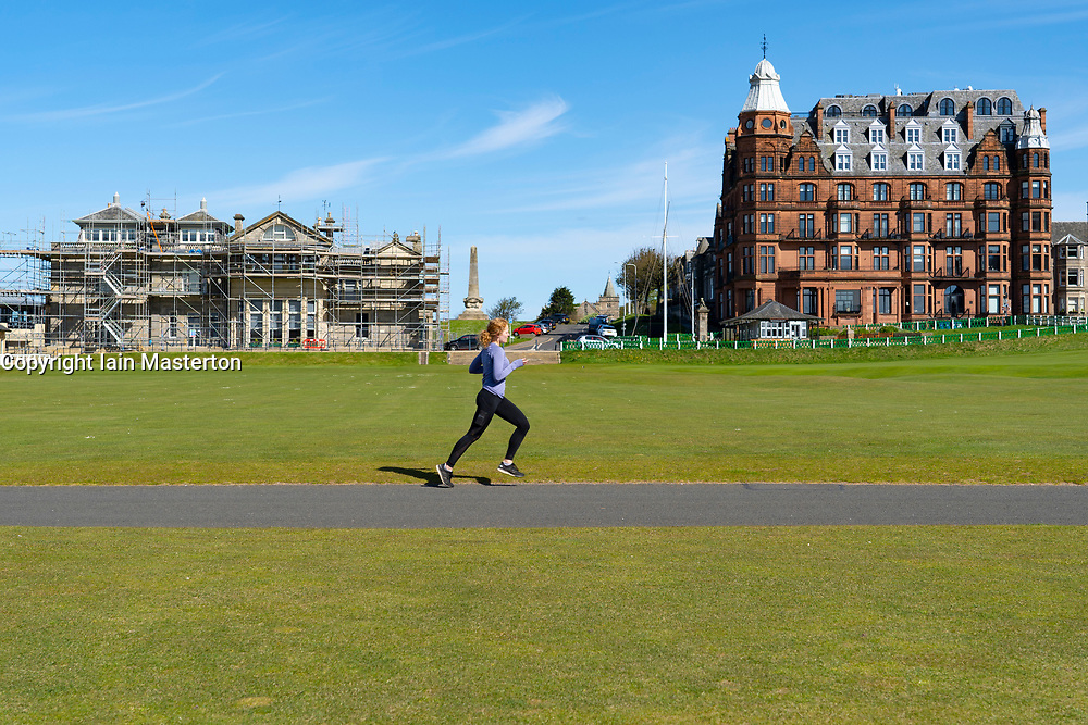 St Andrews, Scotland, UK. 4 May 2020.  The famous Old Course at St Andrews is closed due to the coronavirus lockdown. Locals are making the most of the closed golf course by using it as a park for they daily exercise. Woman runs across first and eighteenth fairways.  Iain Masterton/Alamy Live News