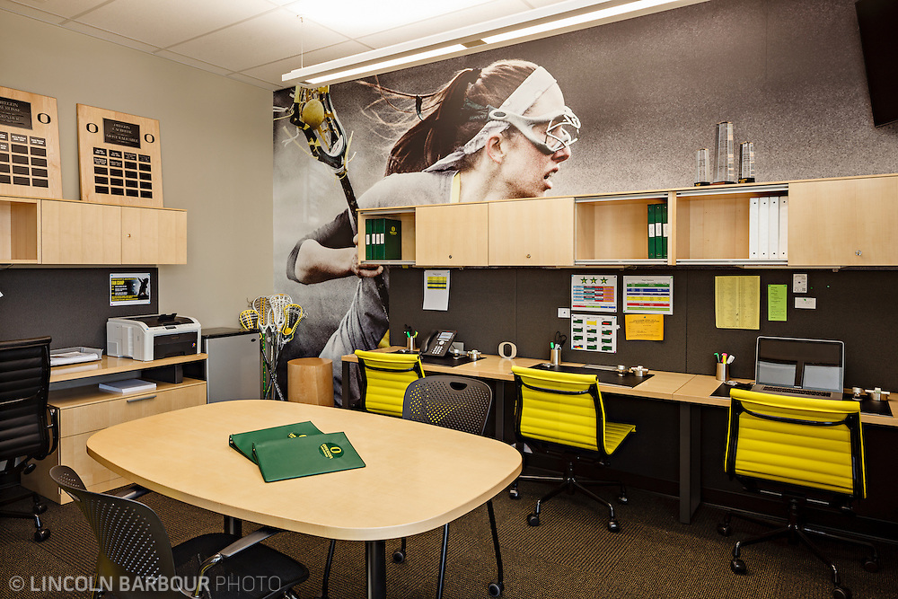 Architectural photo of University of Oregon's Women's Soccer & Lacrosse Stadium. Designed by DLR Group. Looking into an administration room.  Desks along the walls and a small table in the middle. Filled with team spirit, yellow and green.
