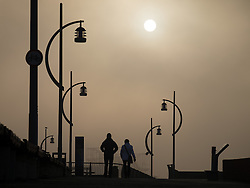 © Licensed to London News Pictures. 30/12/2016. Portsmouth, UK.  A couple walking along the promenade in Old Portsmouth. People on the South Coast have woken up to foggy weather this morning, 30th December 2016. Photo credit: Rob Arnold/LNP