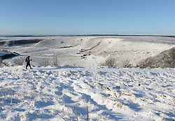 © Licensed to London News Pictures. 15/01/2016. North Yorkshire Moors, UK. A walker takes a path through the snow at the Hole of Horcum on the North Yorkshire Moors. Photo credit : Anna Gowthorpe/LNP