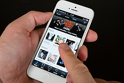 Close-up detail of man holding new iPhone 5 smart phone showing iTunes music store
