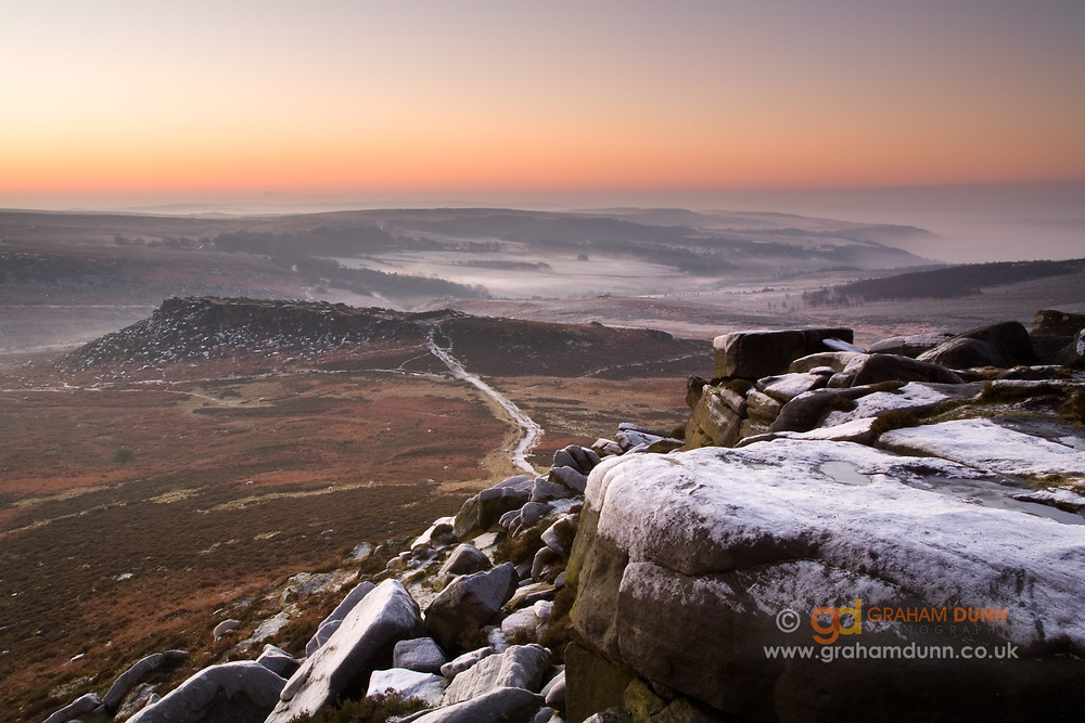 Heavily frosted boulders on Higger Tor overlook Carl Wark, an Iron Age Hill fort, on Hathersage Moor. A frosty white path connects these two iconic features in the Peak District. A winter landscape scene in England, UK.