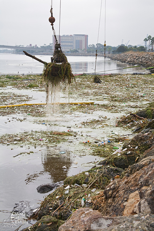 Cranes picking up garbage debris after first rain of the season. The Garbage boom on the Los Angeles River in Long Beach was built in 2001. Urban runoff carries an assortment of trash and debris from catch basins where a network of pipes and open channels create a pathway to the Ocean. The man made debris can include plastic bags and bottles, Styrofoam cups, cans, tires, and household furniture. After the first major storm of the season, the boom may collect over 50,000 pounds of trash.