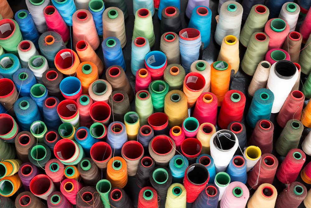 Sewing threads multicolored in a workshop wall.