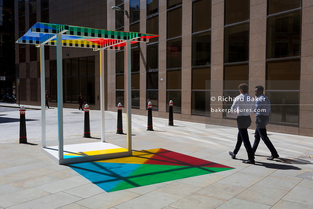 """Art in the City artwork entitled """"4 Colours at 3 Meter High"""" by Daniel Buren leaves multi-coloured patterns from strong sunlight  on the pavement at One Creechurch Place, on 17th Juy 2017, in the City of London, England."""