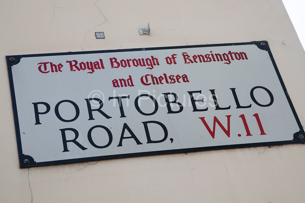 Sign for Portobello Road in Notting Hill, West London, England, United Kingdom. People enjoying a sunny day out hanging out at the famous Sunday market, when the antique stalls line the street.  Portobello Market is the worlds largest antiques market with over 1,000 dealers selling every kind of antique and collectible. Visitors flock from all over the world to walk along one of Londons best loved streets.