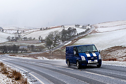 © Licensed to London News Pictures. 02/03/2016. Brecon, Powys, Wales, UK. On the second day of Spring, vehicles negotiate the B4520 'Brecon Road' on the high moorland of the Mynydd Epynt range between Brecon and Builth Wells, Powys during a blizzard of snow, sleet and small hailstones with winds gusting up tto 50 mph. Photo credit: Graham M. Lawrence/LNP