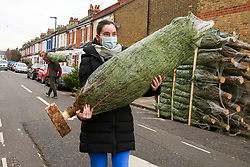 © Licensed to London News Pictures. 02/12/2020. London, UK. A woman wearing a face covering purchases a real Christmas tree in north London as COVID-19 lockdown restrictions are lifted. From today, 2 December, England returns to tiered COVID-19 restrictions, allowing non-essential businesses to re-open. Photo credit: Dinendra Haria/LNP
