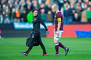 Hearts club medic, Karen Gibson leaves the field with Steven Naismith (#14) of Heart of Midlothian during the Betfred League Cup semi-final match between Heart of Midlothian FC and Celtic FC at the BT Murrayfield Stadium, Edinburgh, Scotland on 28 October 2018.