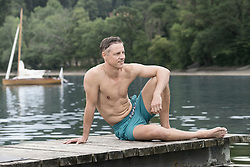 Mature man sitting on wooden pier and smiling, Bavaria, Germany