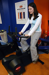 Young woman using an upright cycle at an inclusive fitness gym ,