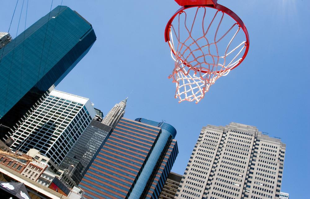 Una canasta de baloncesto en South Street se perfila contra el cielo azul de de Manhattan, con los edificios del distrito financiero al fondo.