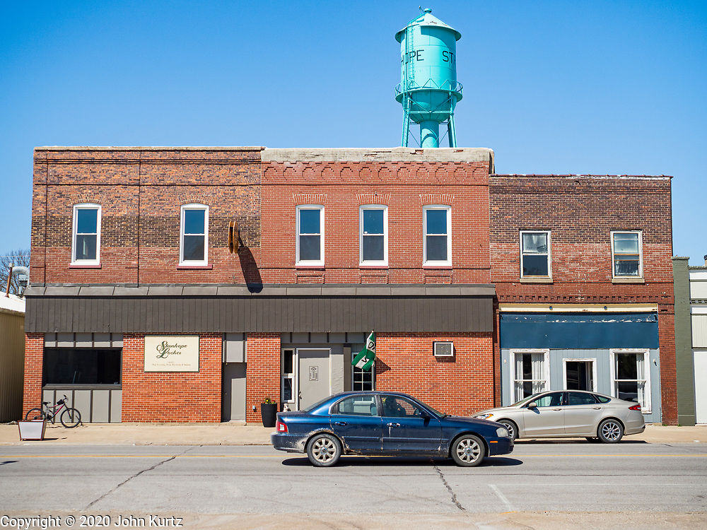 30 APRIL 2020 - STANHOPE, IOWA: A motorist drives past Stanhope Locker and Market, in Stanhope, Iowa. The family owned meat locker slaughters and butchers beef cattle, pigs, and sheep. The COVID-19 (SARS-CoV-2/Coronavirus) pandemic has spread among employees in the meat packing plants in the Iowa, Nebraska, South Dakota, and Minnesota, forcing many to close or curtail operations. This has resulted in farmers euthanizing thousands of pigs and beef cattle. Pork production has been slashed by about 40% because of the pandemic. Meat lockers and family owned butchering facilities have been swamped with farmers and ranchers trying to sell their livestock to them rather than the meat packing plants, but the meat lockers are backed up by the huge increase in supply. Many meat lockers are now full through the end of the year. Stanhope Locker and Market doesn't have any openings for slaughtering and butchering either cattle or pigs until mid-December 2020.         PHOTO BY JACK KURTZ