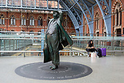 The statue of poet John Betjeman 2007 by Martin Jennings looks upwards in the main concourse at St. Pancras Station, on 10th April 2018, in London, England.